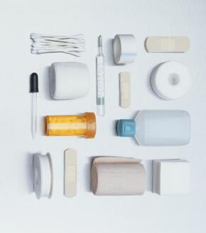 Overhead view of first aid kid items on white background