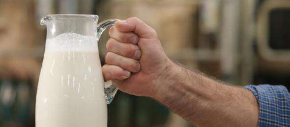 man-holding-out-pitcher-of-milk