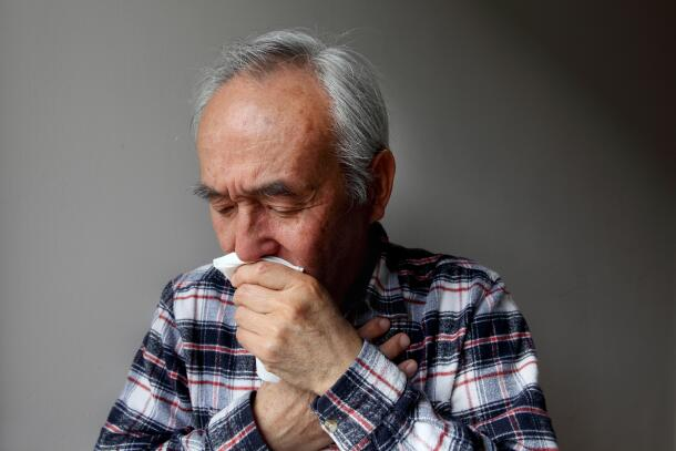 man-coughing-into-napkin