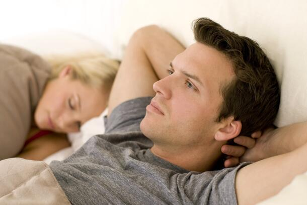 Man in bed with hands behind head next to a sleeping woman