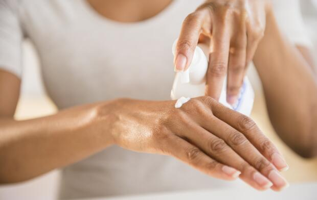 woman-putting-moisturizer-on-hand