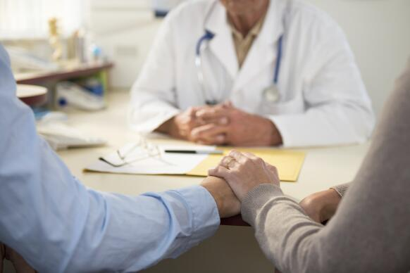 Worried mature couple with doctor