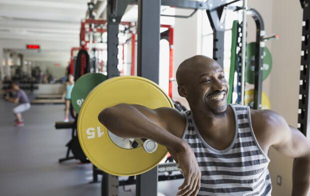 Enthusiastic man leaning on barbell at gym