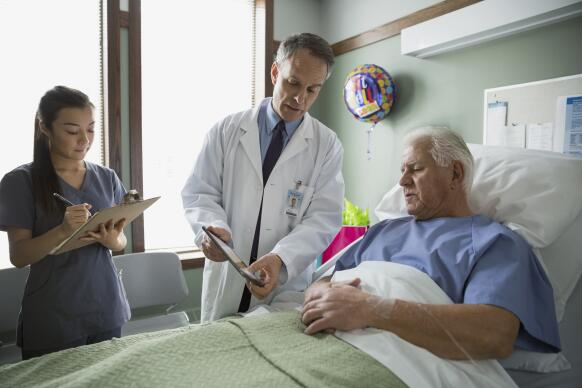 Doctor showing patient digital tablet in hospital room