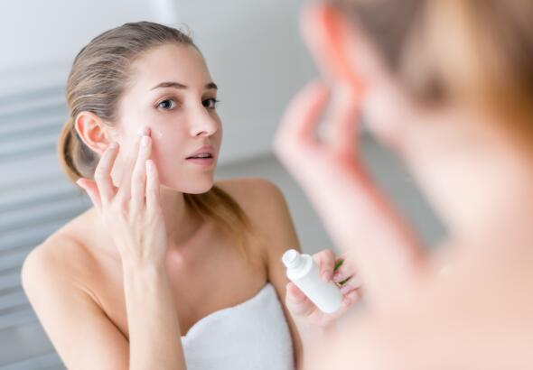 Young woman applying cream