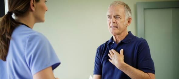 Man with hand on his chest, seeing doctor