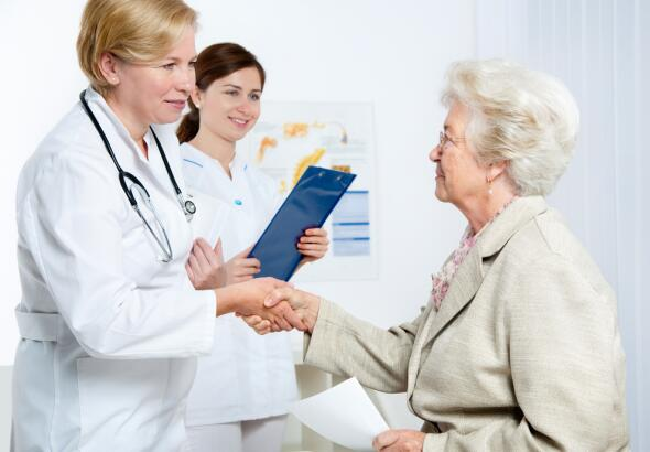 Senior woman shaking hand with doctor