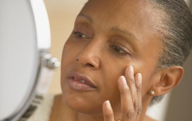 middle age African American woman looking at skin in mirror