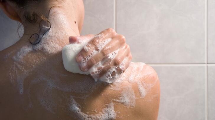 Women in shower with bar of soap in hand