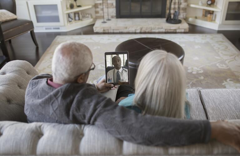 senior Caucasian couple sitting on living room couch holding up tablet with telehealth doctor's appointment
