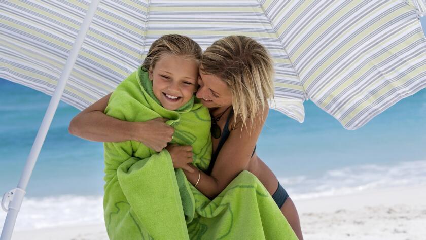mother embracing daughter under sunshade