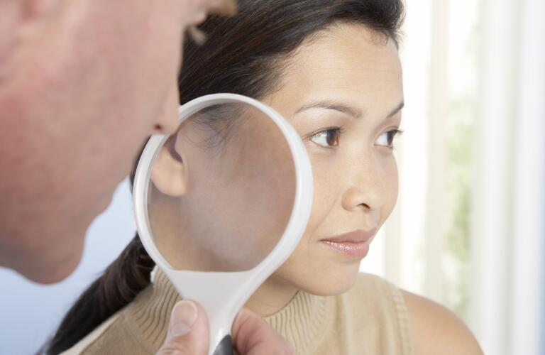 dermatologist-looking-at-patients-skin-with-magnifying-glass