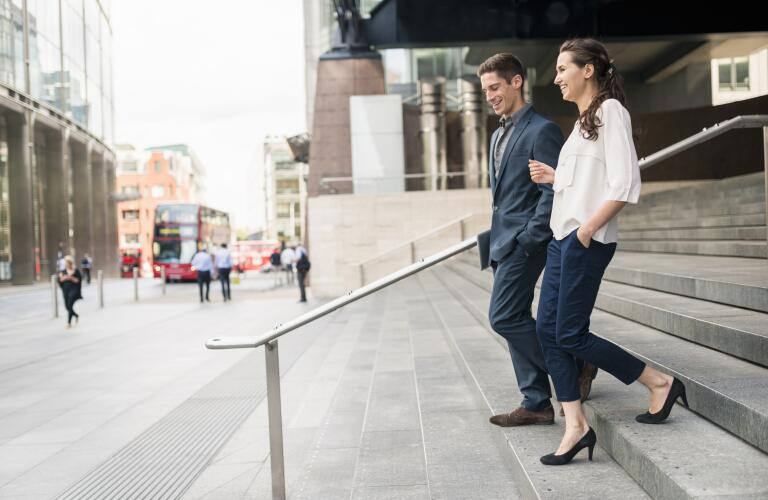 Rear view of young businessman and woman chatting whilst walking down stairway, London, UK