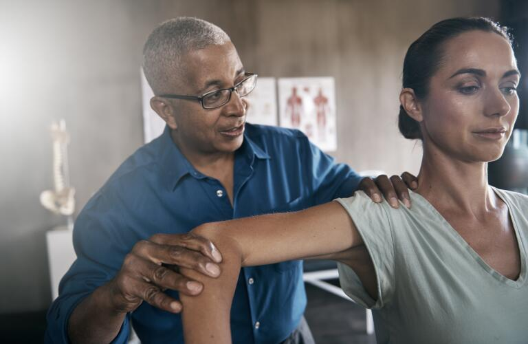 physical-therapist-examining-womans-shoulder