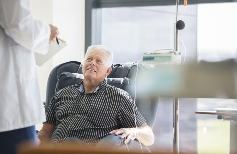 senior Caucasian male receiving chemotherapy in hospital speaking with doctor