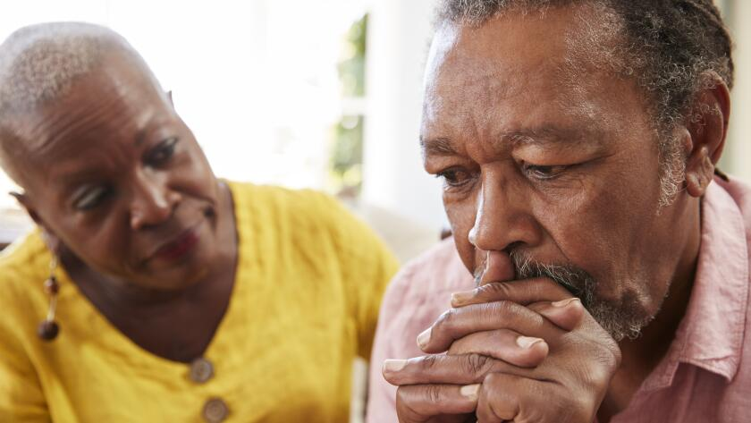 Senior African American man looking concerned while senior African American woman comfort hims