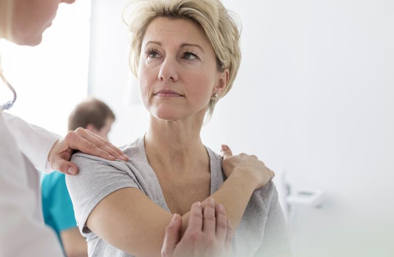 woman-holding-shoulder-at-doctors-appointment