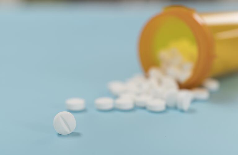 small, white, round tablets spilling from medicine bottle on blue background, closeup