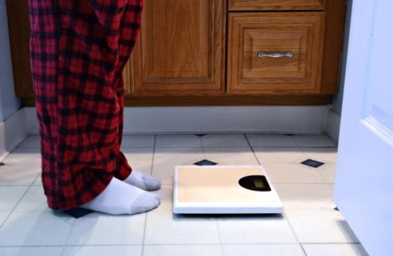 Man Standing in Front of Bathroom Scale