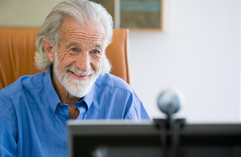 senior man smiling at computer webcam