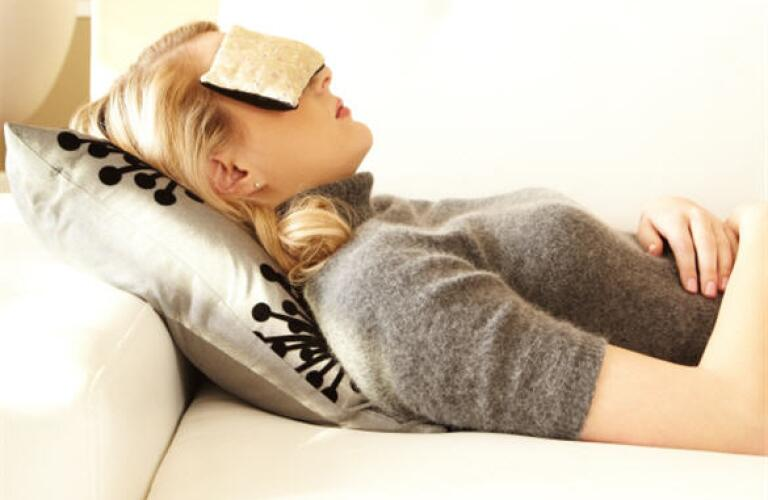 woman laying down with cloth on eyes