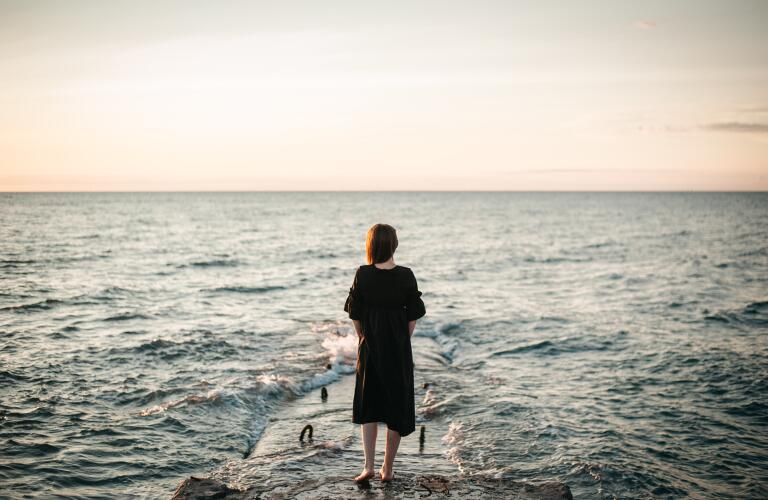 Young woman standing on rock looking at ocean