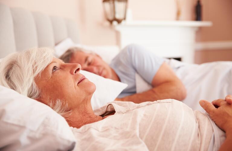 Older Caucasian woman lying awake in bed next to sleeping husband