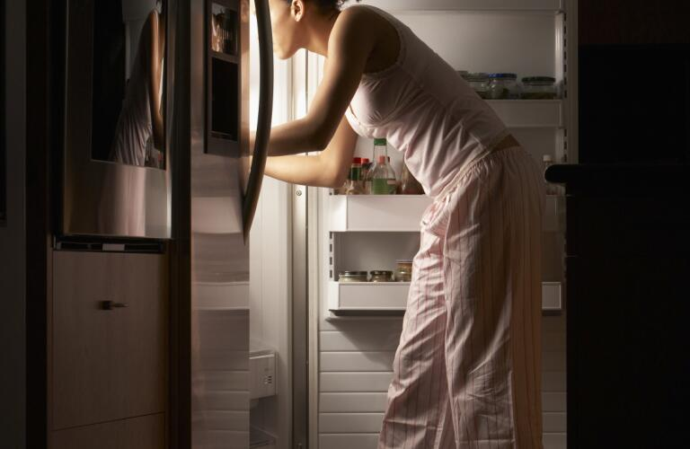 woman standing in front of fridge