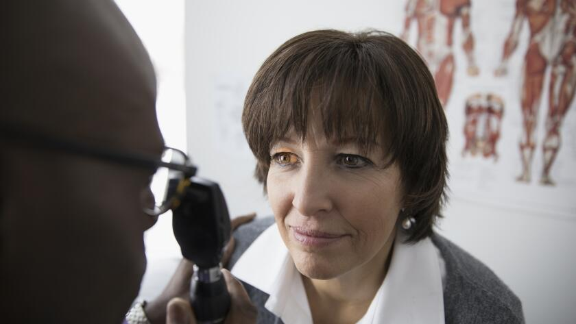 male African American eye doctor examining eyes of middle aged female Caucasian female
