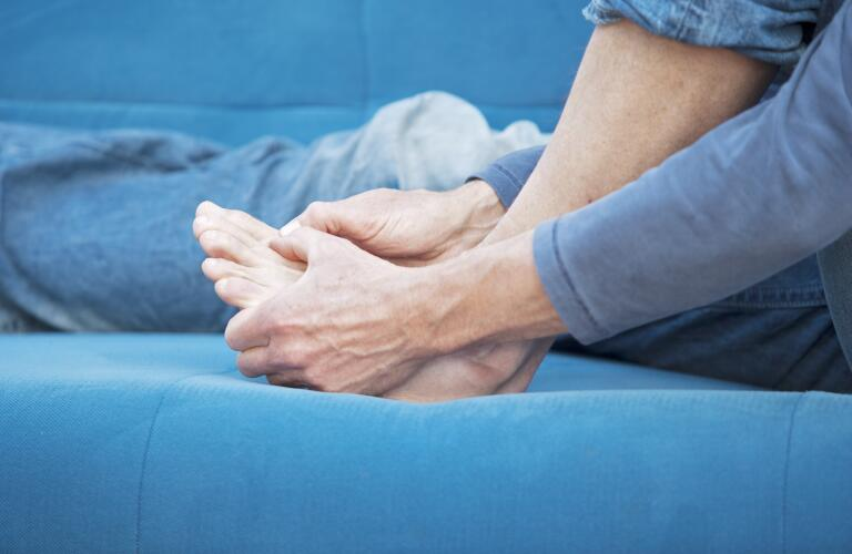 man holding big toe and foot in pain