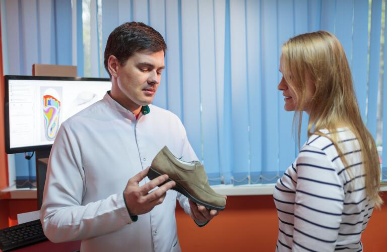 Podiatrist showing orthopedic shoe to patient