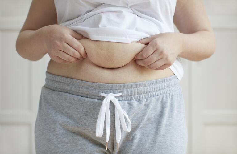 Unseen Caucasian woman holding belly fat