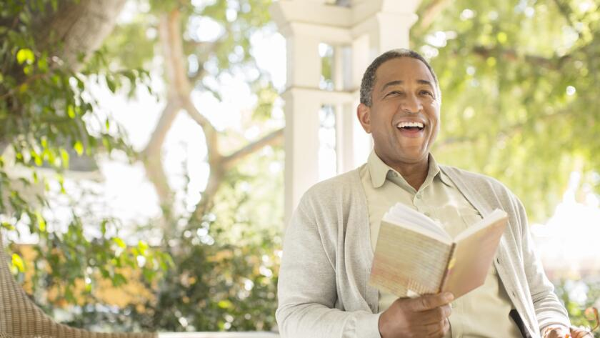 laughing-senior-man-reading-on-porch