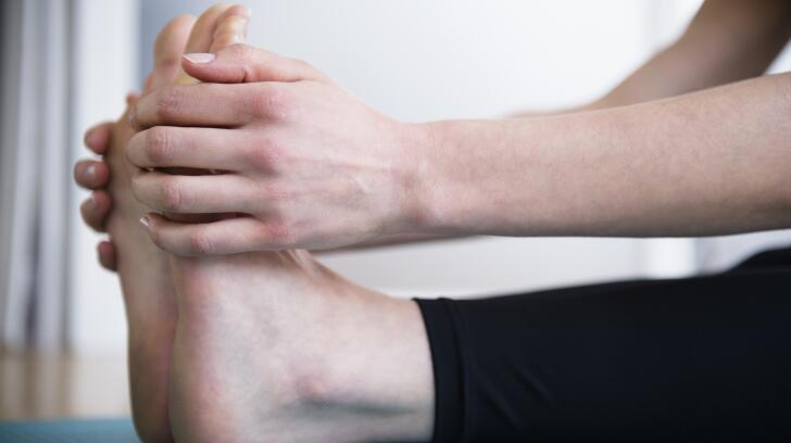 женщина-растяжка-ноги-держась-ступни