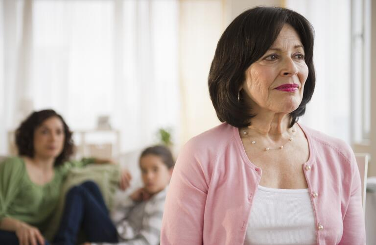 Older Hispanic woman looking concerned with daughter and granddaughter in background