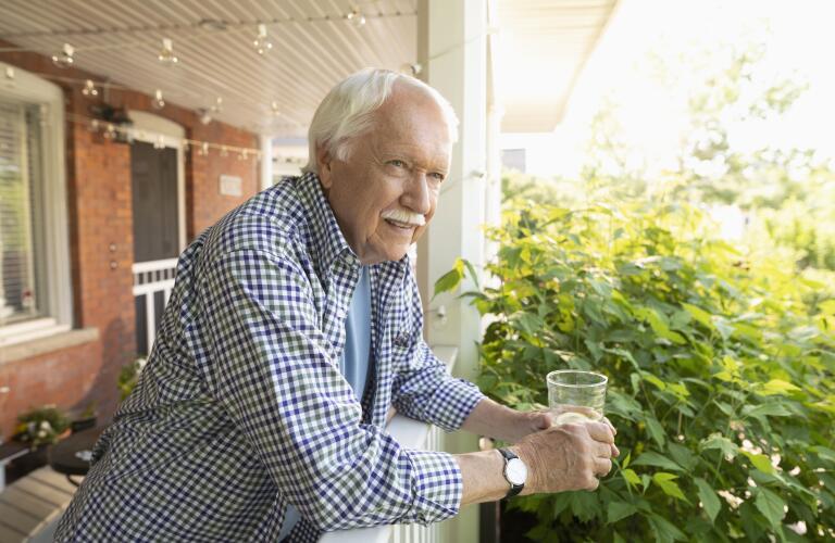 Senior Caucasian man drinking water or lemonade on front porch