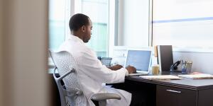 African American male doctor typing on laptop at desk in office