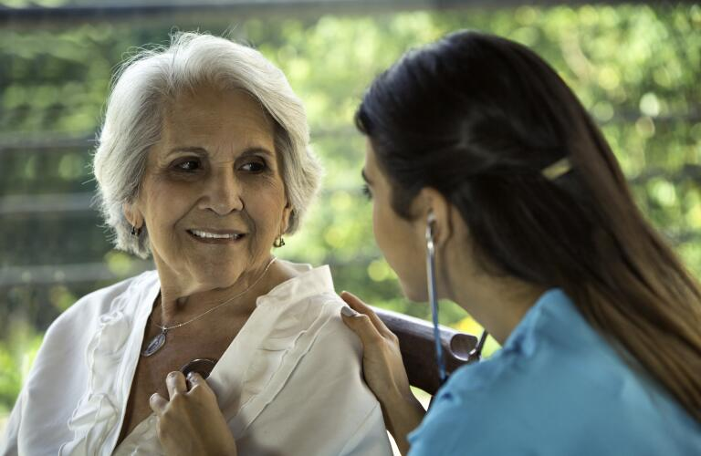 Female physician listens to senior patient's heart