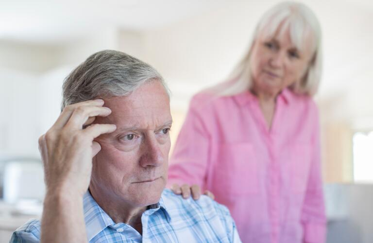 Senior Caucasian male looking concerned or stressed while senior Caucasian woman comforts him in background