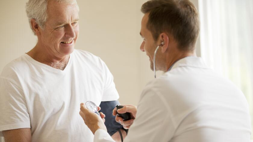 Doctor checking patients blood pressure