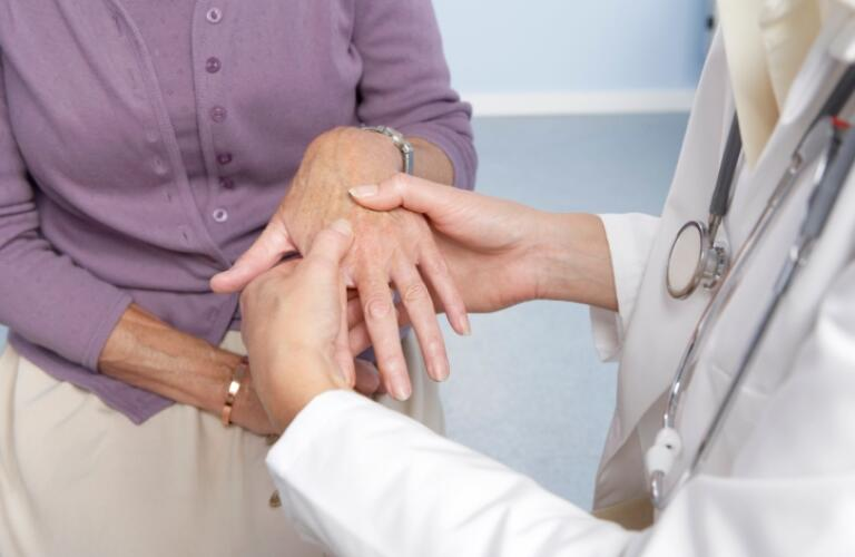 General Practitioner examining patients hand