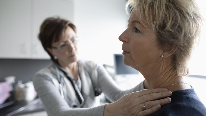 female doctor examining female patient's neck and shoulder