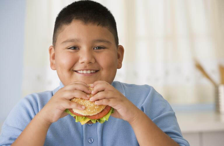 boy eating hamburger in kitchen