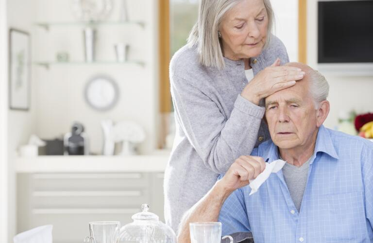 Older woman feeling sick husband's forehead