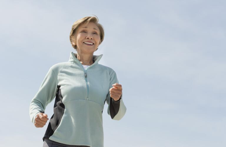 Middle-aged woman jogging outside