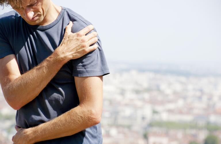 Man outdoors holding shoulder in pain
