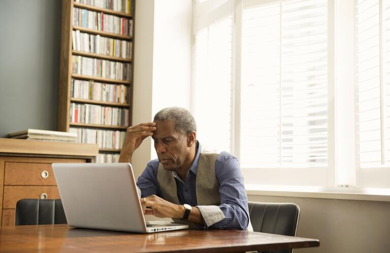 senior African American man sitting in office study looking at laptop