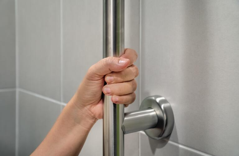 closeup of hand holding onto shower grab bar