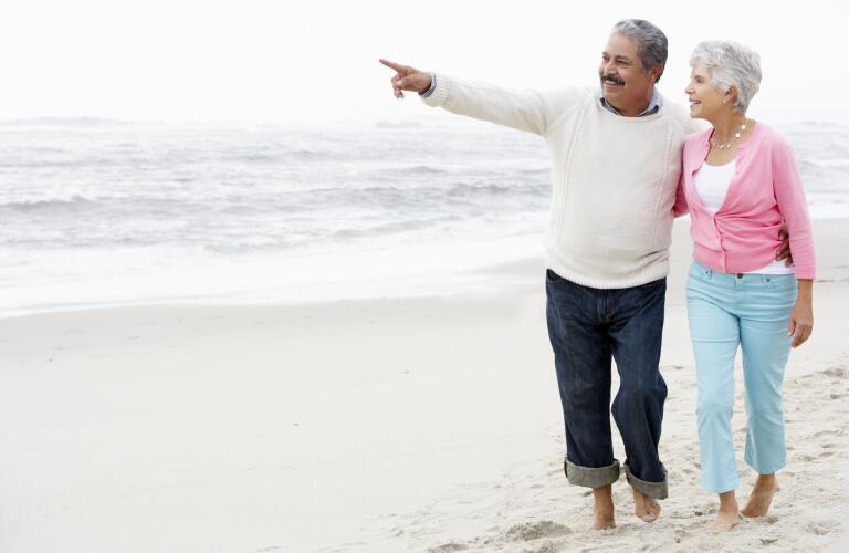 senior-couple-walking-on-beach