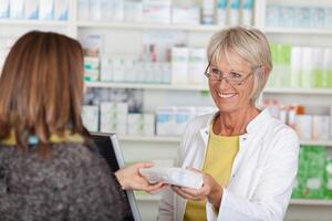 Women picking up prescription at pharmacy